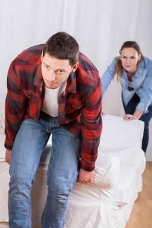 young couple moving the couch in new flat