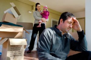 family beside moving boxes - victims of a moving scam