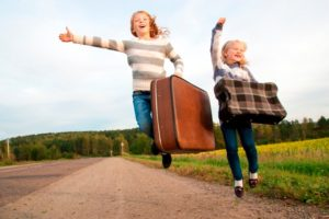 2 girls with suitcase beside the road ready to travel
